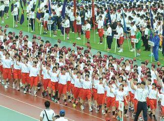 県高校総体開会式で行進する選手たち=29日、県総合運動公園陸上競技場
