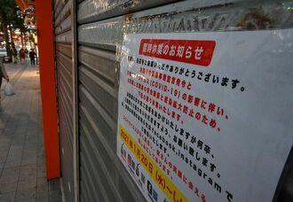 県独自の緊急事態宣言を受け、臨時休業に入った国際通りの土産品店=20日午後6時すぎ、那覇市松尾