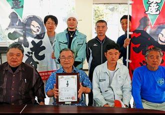 「大宜味産和そば」の商標登録証を手にする山城会長(前列左から2人目)と平良会長(前列左)ら=11日、大宜味村