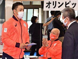 県空手連盟の平良慶孝会長から激励金を受け取る喜友名諒選手(左)