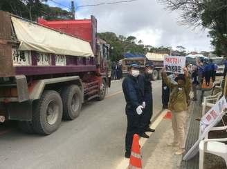 N1ゲートに入る工事車両とヘリパッド建設に反対の声を上げる市民ら=16日午前10時半ごろ、東村高江