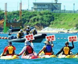 カヌーでスパット台船に近づき、掘削調査に抗議する市民ら=18日午前9時57分、名護市辺野古沖(田嶋正雄撮影)