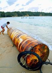 浜に打ち上げられた鉄管。ドラム缶3つ分ほどの長さがある=26日午後5時半ごろ、名護市安部