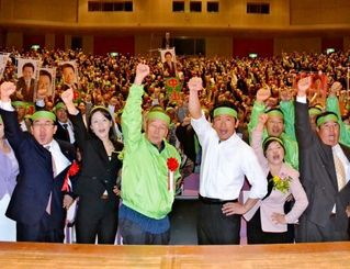 必勝を誓い、拳を振り上げる中山義隆氏(中央右)や支援者=石垣市民会館大ホール
