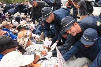 座り込む市民を強制排除する機動隊員=21日午前10時半、東村高江