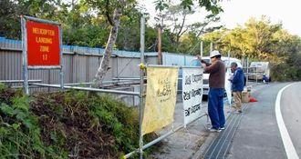 仮設テントが撤去された場所に新たに横断幕を取り付ける住民ら=20日、東村高江