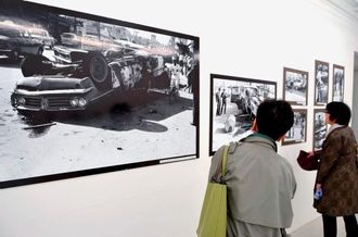 焼け焦げた米人車両の写真を鑑賞する来場者=10日、沖縄市中央のギャラリーM&A