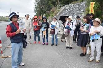 ゲート前で稲嶺進前名護市長(前列左端)から説明を聞く日本ペンクラブのメンバー=19日午後2時2分、名護市辺野古米軍キャンプ・シュワブゲート前