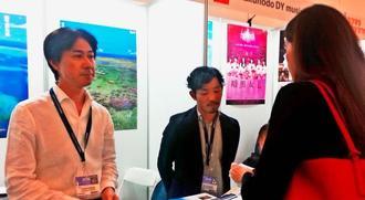 フィルムマーケットの沖縄ブースで沖縄での撮影について説明する新川さん(左)と砂川さん=米サンタモニカ市