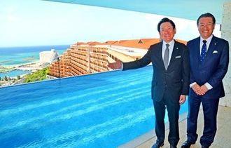 海を見渡せる最上階のプールをPRするKPGの加藤友康代表(左)とKPGホテル&リゾートの田中正男取締役社長=21日、恩納村のカフーリゾートフチャク コンド・ホテルのアネックス棟