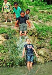 夏日の下、水遊びを楽しむ「風の子学童」の子どもたち=6日午後、南城市玉城・垣花樋川(長崎健一撮影)