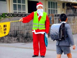 メリークリスマス―。登校する子どもたちの安全を願って、けさも街頭に立つ知花賢宜さん。クリスマスのきょうは特別にえんぴつのプレゼントが子どもたちを喜ばせた=25日午前7時45分、嘉手納町水釜