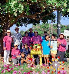 デイゴの木の下で笑顔を見せるひまわりサークルと平敷子ども会の児童ら