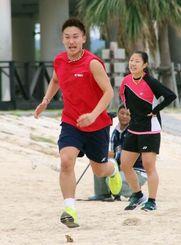 バドミントンの日本代表合宿で、砂浜を走る桃田賢斗。右は奥原希望=11日、沖縄県糸満市