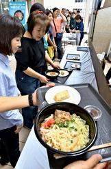 沖縄そばの受け取り口で列をつくる来場客=15日午後、那覇市・タイムスビル1階エントランス