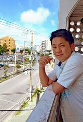 ガソリンスタンドがあった場所を自宅アパートから見る上原一将さん=7月31日、宜野湾市佐真下