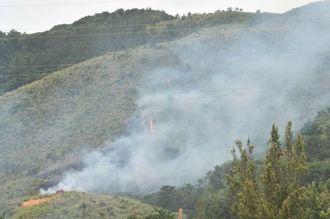 山の斜面に白煙が立ちこめる米軍キャンプ・ハンセンの演習場内。炎が上がっているのも確認できる=14日午後0時57分、沖縄自動車道屋嘉IC付近から撮影