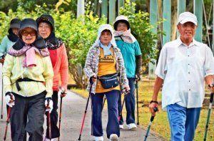 元気にノルディックウオーキングをする「ちょ筋教室」の参加者=11日、中城村吉の浦公園