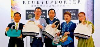 琉球紅型・首里織とポーターが共同開発したバッグを披露する糸数社長(左から2人目)ら=17日、デパート・リウボウ