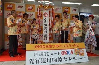 沖縄ICカード「OKICA」がモノレールで先行運用されることを祝う仲吉良次社長(左)ら=20日、ゆいレール那覇空港駅