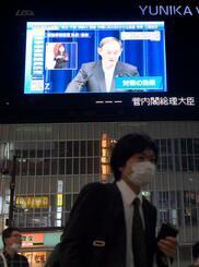 緊急事態宣言を月末まで延長し、4都府県に愛知、福岡両県を追加することを決め、記者会見する菅首相を映し出す大型ビジョン=7日午後、東京・新宿
