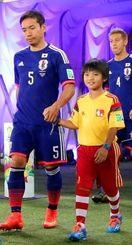 憧れの長友選手と手をつなぎピッチに向かう國仲藍夢君(右)=20日、ブラジル・ナタルのドゥナス競技場