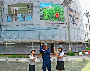 ビーグや闘牛の写真を張った養生シートを背にする、うるま工業の粟國代表取締役(中央)、喜屋武総務課長(右)、湧川さん=3日、うるま市の安慶名交差点近く