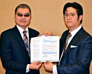 データセンターサービスの向上に向けて協議する協定書を締結した沖縄クロス・ヘッドの渡嘉敷社長(左)と、eASPNetのジェイソン・ホ会長室長兼CEO代理=25日、県庁