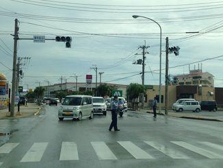落雷で停電し、信号が消えた交差点で交通整理する警察官=石垣市