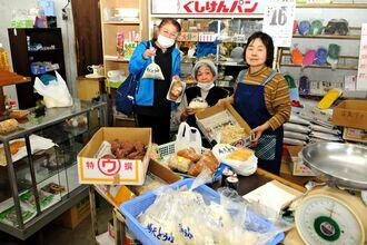 上原商店を切り盛りする上原伴子さん(右)と市内外から豆腐などを買いに訪れた常連客たち=17日、南城市佐敷津波古