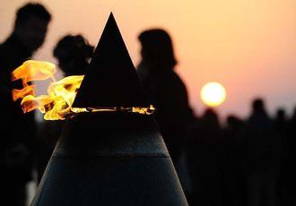 平和の火の向こうから現れた初日の出=1日午前7時29分、糸満市摩文仁・平和祈念公園(我喜屋あかね撮影)
