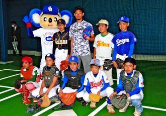 投球練習場の落成式でピッチングを披露した中日の又吉克樹投手(後列中央)と少年野球の子どもたち=北谷公園