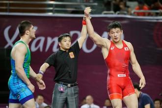 男子フリー92キロ級3位決定戦で勝利した松本篤史(右)=西安(共同)
