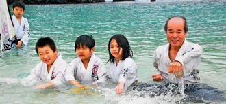水中で空手の稽古をする子どもたち=那覇市・波の上ビーチ
