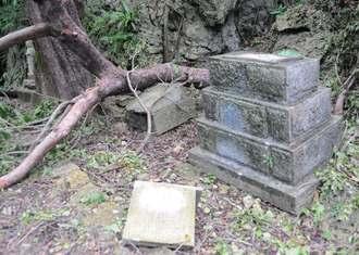 糸満市摩文仁の突風で、沖縄師範健児之塔そばで起きた倒木が当たり、基部から落ちたとみられる石碑(手前)=20日、同所