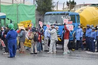 基地から出てきた工事車両に「工事はやめて」と抗議する市民=12日午前9時40分、名護市辺野古の米軍キャンプ・シュワブゲート前