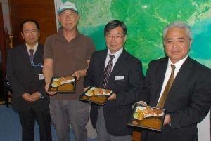 やんばるスパイスカレーの発売をPRする「やんばる畑人プロジェクト」の芳野幸雄代表(左から2人目)ら=24日、名護市役所