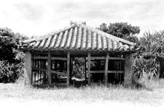 久高島で12年に1度行われる祭事「イザイホー」の場、久高殿の「神アシャギ」。今も同じ場所にある。島に詳しい赤嶺政信・琉球大学教授は「祭事の前には神アシャギ周りの草を刈るため、写真ほど伸びることはない」と語る。朝日新聞「海洋ニッポン」連載よりも前で、祭事の間が空いて草が茂る時期であることから、「35年5月ごろの取材だったのでは」とみている(写真:朝日新聞社)
