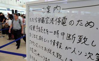 停電のため搭乗手続きの遅れを伝えるホワイトボード=9日午前8時半、那覇空港