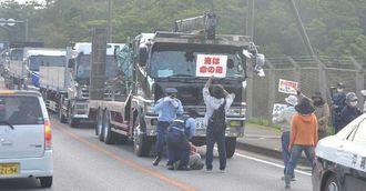 キャンプ・シュワブに機材を搬入する大型トラックを止めようとする市民と排除する県警=8日、名護市キャンプ・シュワブ前