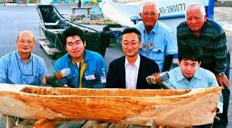 マルキンニ(丸木舟)を、石おので製作した日本工業大学の学生らとハマスーキのメンバー=市西崎町・糸満海のふるさと公園