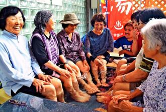 「ギンバル温泉」の足湯を楽しむ人たち。心地よさに会話も弾む=2日、金武町伊芸地区公民館