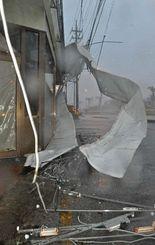 暴風で壊れ、あおられる看板=11日午後、読谷村伊良皆