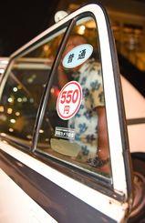 初乗り運賃が550円に引き上げられた普通車のタクシーに乗る乗客=1日、那覇市久茂地