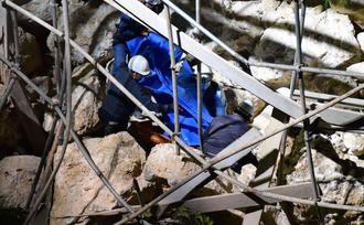積み石が崩れた現場で、捜索作業する消防隊員=15日午後7時50分、北中城村安谷屋(勝浦大輔撮影)