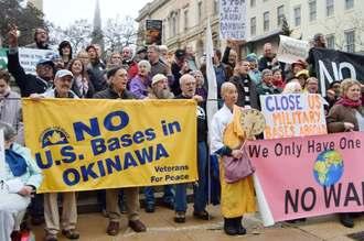 12日、米ボルティモアで「沖縄に米軍基地はいらない」などと書かれた横断幕を持ってデモをする人たち(共同)