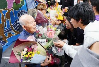 87歳で夜間中学校を卒業し、在校生やスタッフから花束を贈られる具志堅政雄さん=8日、那覇市樋川の珊瑚舎スコーレ(鈴木実撮影)