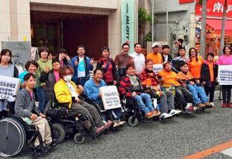 小雨がぱらつく中、沖縄型神経原性筋萎縮症の治療法開発などを求める署名を街頭で呼び掛けるメンバー=14日午後、那覇市・国際通り