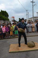雨を願いカンドーラ―石を持ち上げる小浜島の若者=竹富町小浜