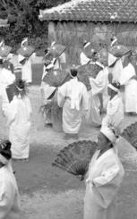1978年のイザイホー4日目「グゥキマーイの踊り」。神アサギ(奧)は、アダンの葉で覆われている。本祭りは旧暦11月15日から4日間。『神々の古層(5)主婦が神になる刻 イザイホー(久高島)』(比嘉康雄、1990年)の主祭場略図には「見物人・取材者席」が見える。78年は人口400人足らずの島を千人以上が訪れたという証言もある